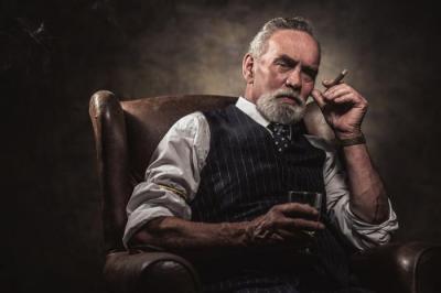 Alter Mann mit Zigarre und Glas